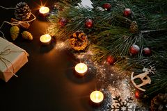 Christmas. Xmas toys, burning candles and spruce branch on black background top view. Space for text Stock Images
