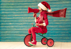 Christmas Xmas Winter Holiday Concept. Happy child rides a bike. Kid playing at home. Christmas Xmas winter holiday concept Stock Image