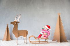 Christmas Xmas Winter Holiday Concept. Happy child riding Christmas sleigh. Kid having fun at home. Xmas holiday concept royalty free stock images