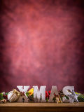Christmas. Xmas word made of wooden letters on a wooden board table. Christmas balls pine cone star fir twig as decoration Royalty Free Stock Images
