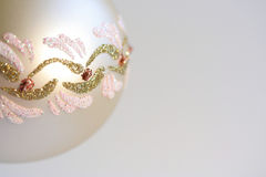 Christmas XXIX. A detail of a pearl-white ball - a piece of Christmas decoration with gold, red and pink lines and spots, light blue background Royalty Free Stock Images