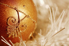 Christmas XXV. A detail of a glittering golden ball - a piece of Christmas decoration lying in white glittering string decoration Stock Photos