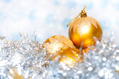 Christmas yellow balls surrounded by tinsel Royalty Free Stock Images