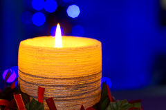 Christmas yellow candle. Christmas candle with blurry lights on background Royalty Free Stock Images