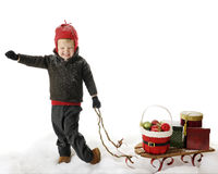 Christmas.  Yes!. An adorable preschooler expressing Yes! as he pulls a sled full of Christmas ornaments and gifts over snow.  Plenty of space for your text over Stock Photos
