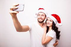 Christmas young beautiful couple in Santa hats in love taking romantic self portrait. Selfie photo together with mobile phone smiling happy wearing on white Stock Photography