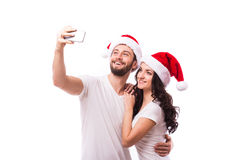 Christmas young beautiful couple in Santa hats in love taking romantic self portrait Stock Photography