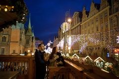Christmas. Young couple from a balcony admires the festive city. Man and women hold the pets in hands Stock Photography