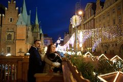 Christmas. Young couple from a balcony admires the festive city. Man and women hold the pets in hands Stock Photos