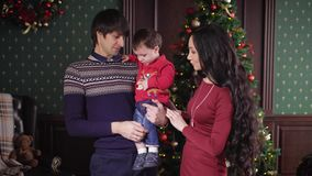 Christmas. Young family with a child getting ready to celebrate the holidays. The room is beautifully decorated, the. Wall is a tree. On the wall hangs a stock video