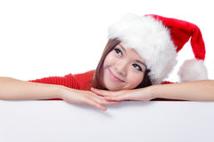 Christmas young girl looking up and thinking. With blank billboard banner sign. Beautiful and cute Asian female model Stock Photography