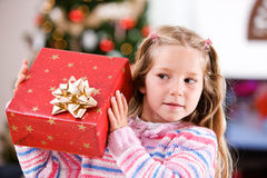 Christmas: Young Girl Tries To Guess What Is In Wrapped Gift. Mother and child in various Christmas themed activities in the home Stock Image