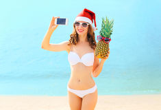 Christmas young smiling woman in red santa hat with pineapple taking picture self portrait on smartphone at beach over sea. Background Royalty Free Stock Image