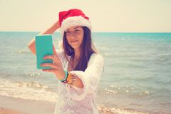 Christmas young smiling woman in red santa hat taking picture self portrait on smartphone at beach over sea background. toned royalty free stock image