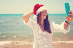 Christmas young smiling woman in red santa hat taking picture self portrait on smartphone at beach over sea background. toned stock photo