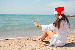 Christmas young smiling woman in red santa hat taking picture self portrait on smartphone at beach over sea background. toned royalty free stock images