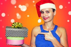 Christmas young woman in hat of Santa Claus points on two gift boxes. Happy girl on Xmas holidays. Purchase gifts on Christmas. Royalty Free Stock Photos