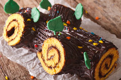 Christmas Yule Log cake decorated with candy sprinkles, on the t Stock Photography