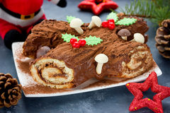Christmas Yule Log cake decorated with chocolate holly mushrooms Stock Image