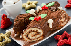 Christmas Yule Log cake decorated with chocolate holly mushrooms Stock Photos