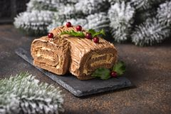 Christmas yule log cake. Traditional chocolate dessert. On festive background stock photography