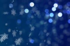 Christmass落在蓝色Bokeh背景的心情雪花 库存图片