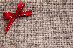 Christmass background with decoration on contrast flax textile. Christmass background with big red bow on contrast flax textile royalty free stock photos