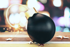 Christmass black small bomb with a lit fuse and golden stars on Royalty Free Stock Photography