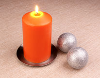 Christmass decorations. Burning candle with christmass decorations over textile background Royalty Free Stock Image
