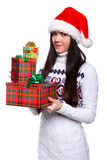 Christmass girl. Smiling young woman in red christmass hat at white background with gifts Stock Photos