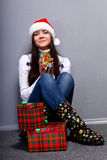 Christmass girl. Smiling young woman in red christmass hat at grey background Royalty Free Stock Photos