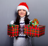 Christmass girl. Smiling young woman in red christmass hat at grey background Royalty Free Stock Image