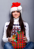 Christmass girl. Smiling young woman in red christmass hat at grey background Royalty Free Stock Images