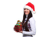 Christmass girl. Smiling young woman in red christmass hat at white background with gifts Royalty Free Stock Photo