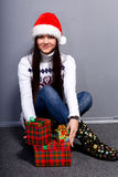 Christmass girl. Smiling young woman in red christmass hat at white background with gifts Royalty Free Stock Images