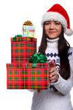 Christmass girl. Smiling young woman in red christmass hat at white background with gifts Stock Image