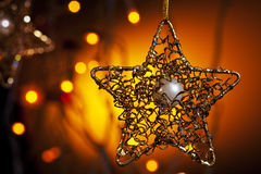 Christmass star. Metal christmass star on warm background and blurry lights Stock Images