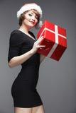 Christmass woman hold gift. Beautiful fashion model. Portrait Stock Photography