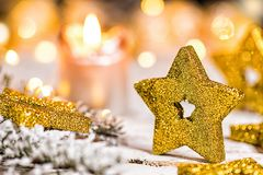 Golden christmas star with fir branch. Golden christmas star with candle, fir branch and lights on old wooden table stock photo