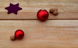 Christmassy background with Walnuts and Red Ball Ornaments on wodden planks.  Royalty Free Stock Photography