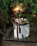 Christmassy Bengal ljus i en kopp av varm choklad med marshmallower, muttrar och kanel på en tappning försilvrar magasinet, selek Arkivbilder