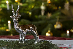 Christmassy Table Decoration. With a silver decoration deer on fir-tree green in front of a Christmas tree royalty free stock image