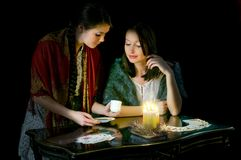 Christmastide fortune-telling. Two girls reading coffee grounds Royalty Free Stock Photography