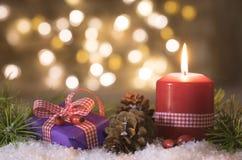 Christmastime. Christmas gift and candle christmastime backdrop with lights bokeh stock photo