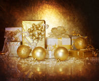 Christmastime gift boxes. Picture of Christmastime gift boxes on dark golden background, luxury Christmas decorations, seasonal shopping, shiny balls, festive stock photography