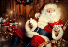 Christmastime. Good old Santa Claus with Christmas gifts at his wooden house. Sepia Stock Photo