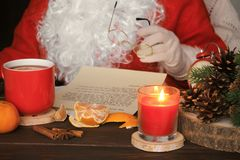 Santa Claus reading letter, drinking tea and eating tangerines. stock images