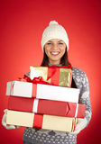 Christmastime. Portrait of lovely girl in winterwear holding heap of packages with gifts royalty free stock photography