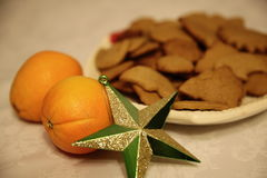 Christmastime table. Close-up of Christmas star decoration, oranges and cookies on a table stock photography