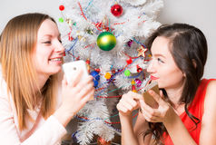 Christmastime, two smiling young girls lying on the carpet in the background a christmas tree illuminated Royalty Free Stock Photo